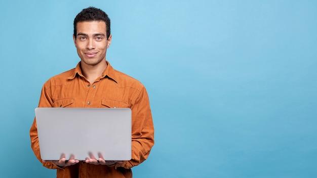 Молодой мужчина держит ноутбук