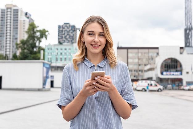Вид спереди красивая девушка держит телефон