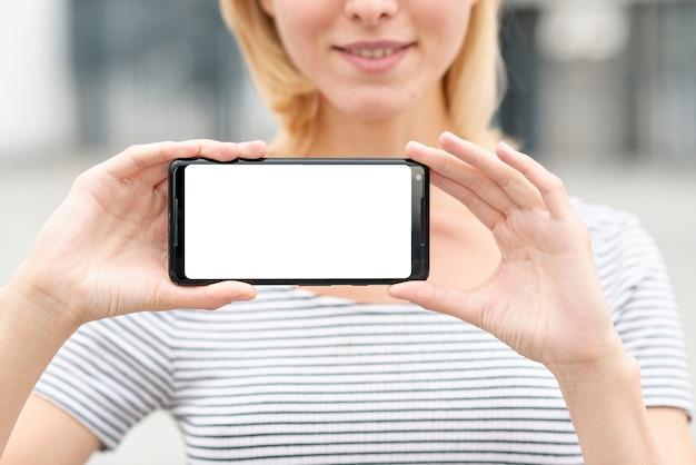 Макро молодая женщина, держащая телефон