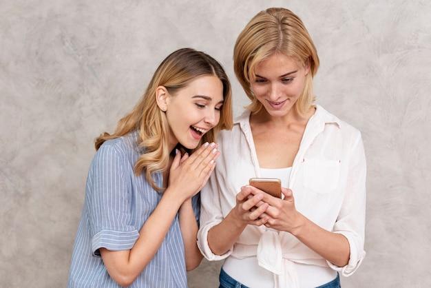 携帯電話をチェックする若い女の子の正面図