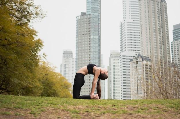 Полный снимок подходит женщина растяжения на открытом воздухе
