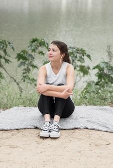 屋外に座っている若い女の子の正面図