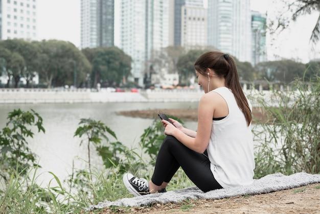 屋外の音楽を聴く若い女性