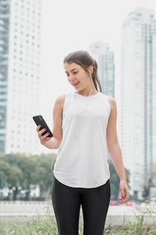 Вид спереди молодая женщина, проверка ее телефон
