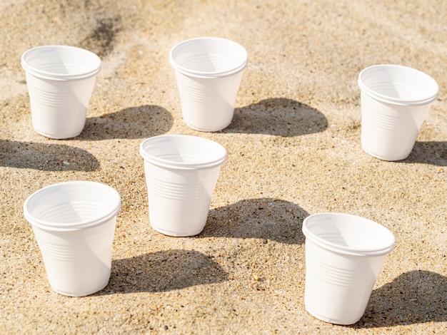 ビーチの砂の上に残ったプラスチックカップ