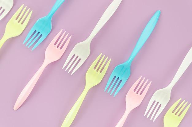 Вид сверху красочные пластиковые вилки на фиолетовом фоне