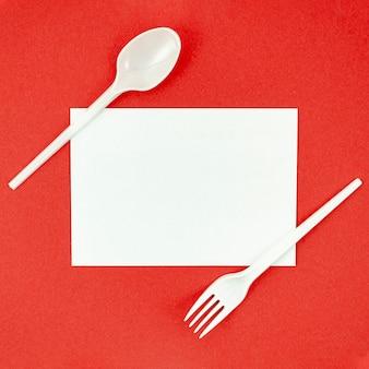 赤の背景にピクニックのためのプラスチック製カトラリー