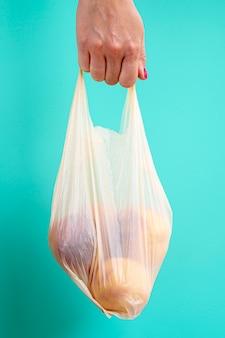 Лицо, занимающее пластиковый пакет с фруктами