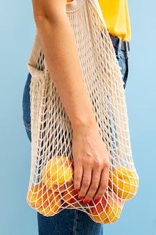 リンゴと白いメッシュバッグを保持している女性