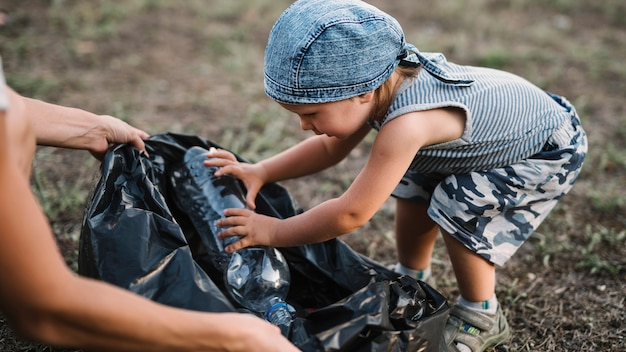 Маленький ребенок кладет пластиковую бутылку в мешок для мусора