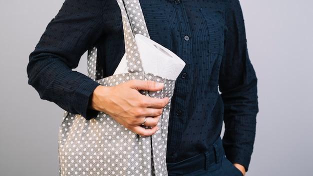 ペーパータオルでバッグを保持しているフロントビュー女性