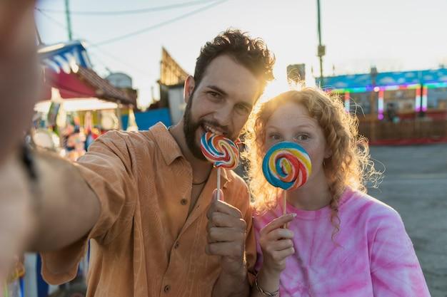 Средний снимок счастливая пара с леденцами, делающими селфи