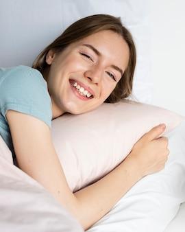 枕を保持している女性を閉じる