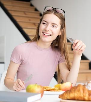 おいしい朝食を持つ女性
