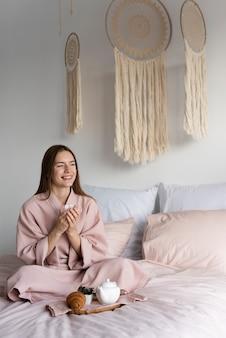 Длинный выстрел женщина в халате, оставаясь в постели