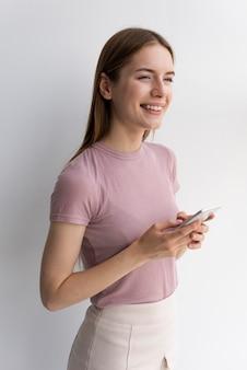 Женщина в розовой футболке стоит и смотрит в сторону