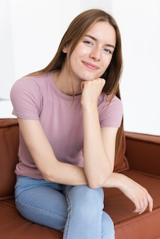 Вид спереди смайлик женщина сидит на диване