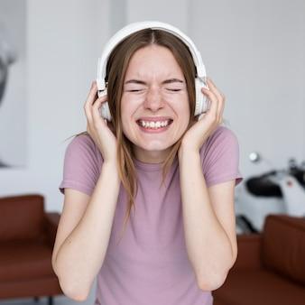 ヘッドフォンで大声で音楽を聴く女性