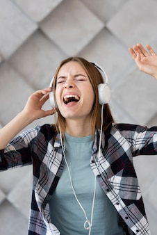 Женщина вид спереди слушает музыку в наушниках