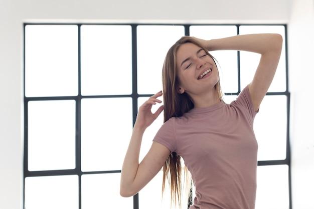 窓の横に立っている笑顔の女性