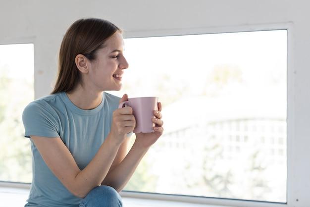 一杯のコーヒーを保持しているサイドビュー女性