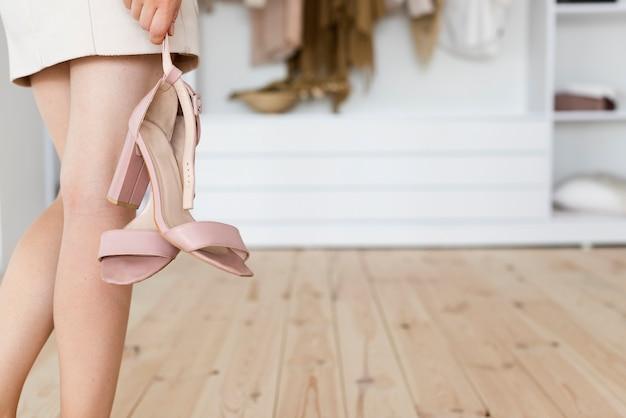 Вид сзади женщина держит ее на высоких каблуках
