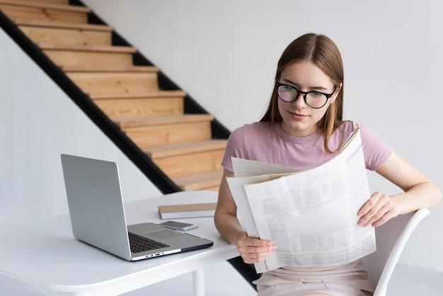 新聞を読んでメガネの女性