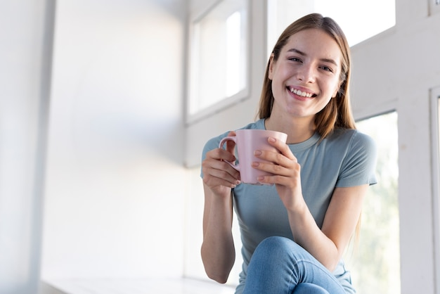 Счастливая женщина держит чашку кофе