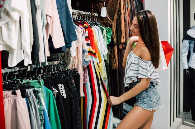 Молодая женщина проверяет брюки в магазине