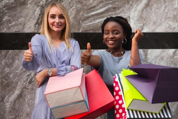 Подружки на покупки, показывая знак ок