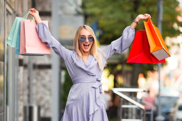 Выходящая молодая женщина с хозяйственными сумками