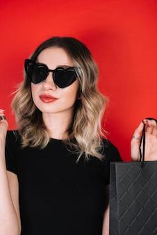 Женщина в очках держит черную сумку для покупок в пятницу