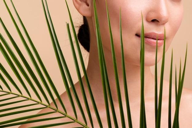 Макро девушка брюнетка позирует с листьями