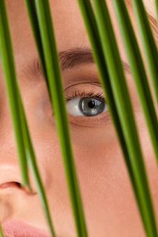 Крупным планом женщина с голубыми глазами и листьями