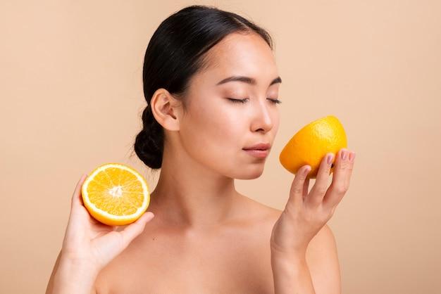 Азиатская женщина крупным планом, улыбаясь половина апельсина