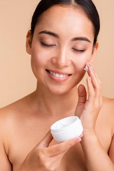 Макро красивая женщина, используя крем для лица