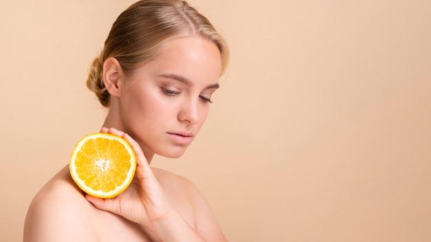 オレンジのポーズでクローズアップ金髪モデル