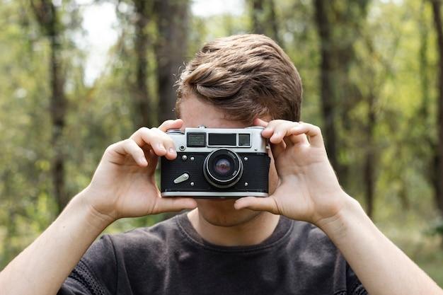 若い男が森で写真を撮る