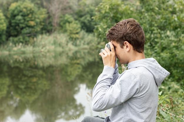 湖の写真を撮るクローズアップショット少年