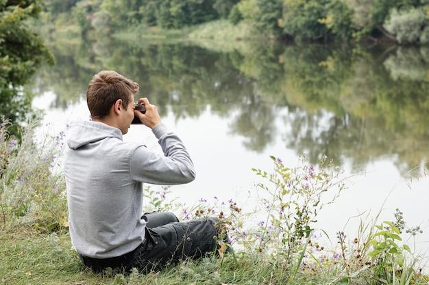 少年は湖の近くで写真を撮る