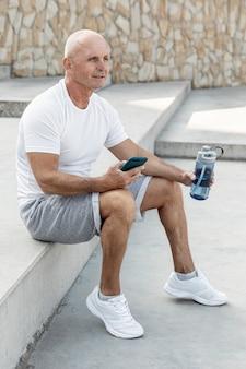 Улыбающийся старший мужчина отдыхает, держа его телефон