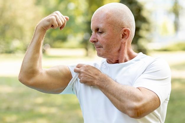 年配の男性が彼の筋肉を噛んで