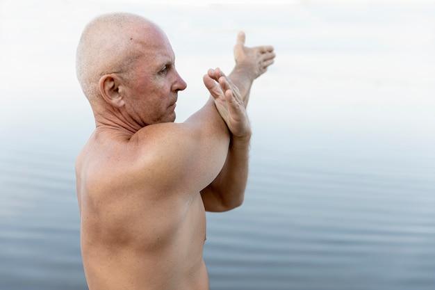 老人が水の近くでストレッチ