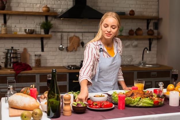 Длинный выстрел женщины, устраивая еду на кухне