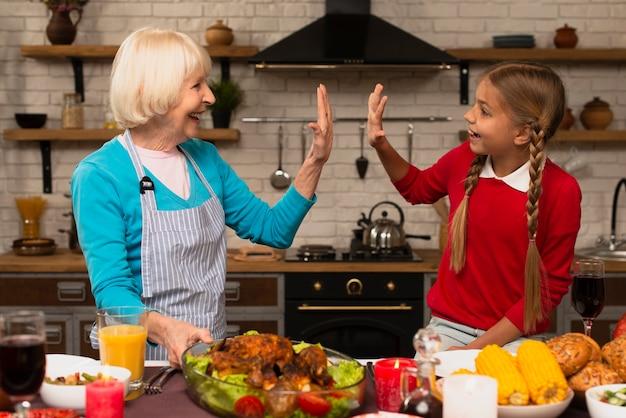 祖母と孫娘が台所で遊んで