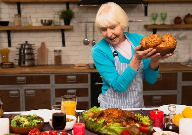 Пожилая женщина держит тарелку с булочкой хлеба