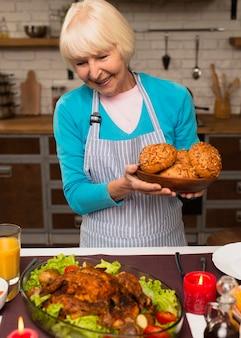 Пожилая женщина держит тарелку с хлебом и смотрит в сторону