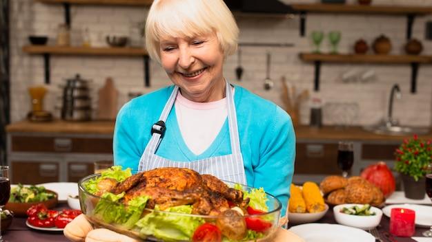 調理されたトルコを保持している高齢者の女性
