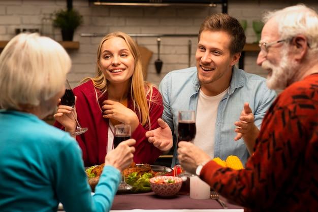 家族のチャットとワインのグラスを保持