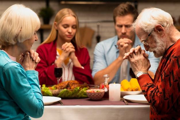 夕食のテーブルの正面で祈る家族